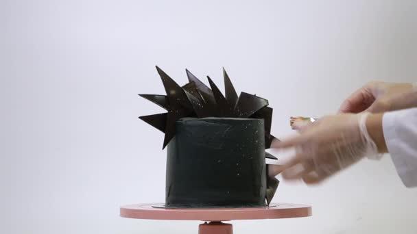 Professioneller Konditor dekoriert eine brutale schwarze Torte mit Schokoladenscheiben auf einem rosafarbenen Ständer. Dessert im futuristischen Stil auf weißem Hintergrund