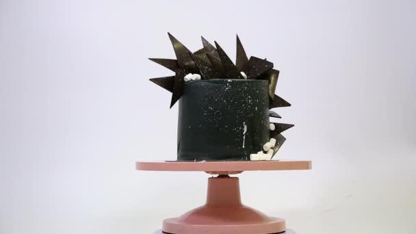 Schwarzer Kuchen mit Schokoladen- und Marshmello-Scheiben rotiert im Kreis auf einem rosafarbenen Ständer. Ungewöhnlich stilvolles Dessert auf weißem Hintergrund. Weltraumkuchen.