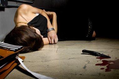 Female murder victim lying on a dark alley