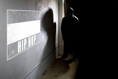 rapper next to wall graffiti