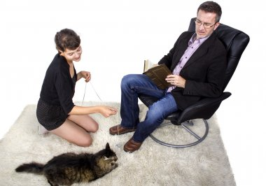 Father and Daughter playing with cat