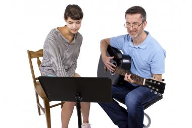 teacher tutoring female play guitar