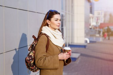 Beautiful brunette woman holding a bag and cup of hot tea or coffee, standing in the street