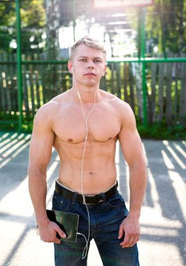 Young athlete stands on the site, listening to music, watching resting sensual, sexy, inflated bodybuilder