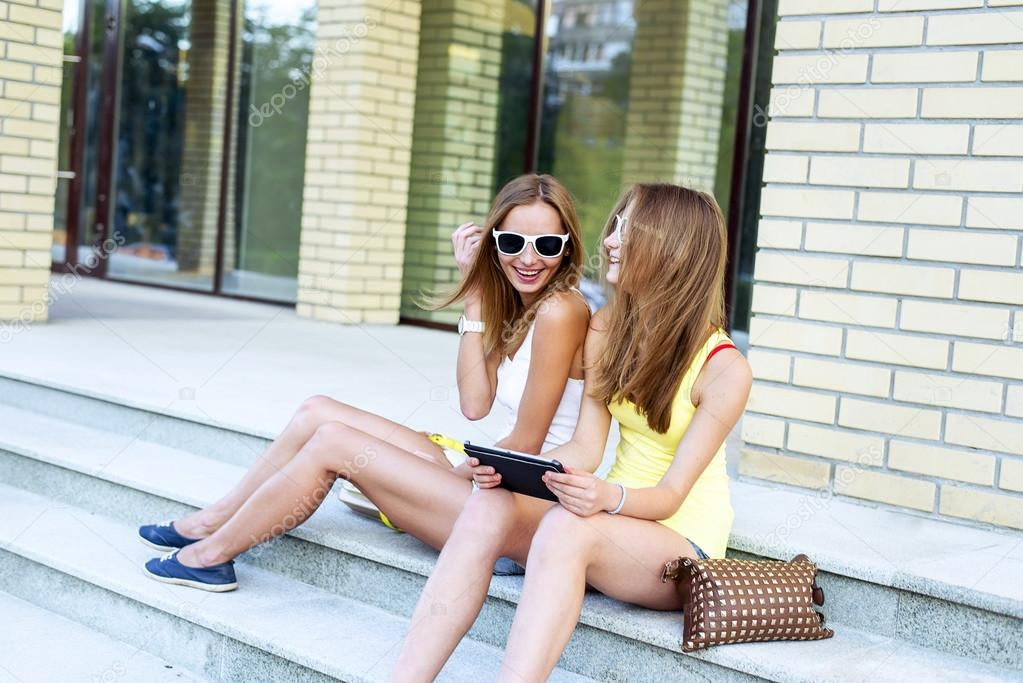 Two sisters steps of the institute laugh happy watching a movie  tablet in social networks glasses, rest, fashion lifestyle girls, teenagers.