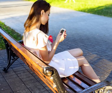 Beautiful girl sitting bench, brunette pink dress, fashion life style with your phone writes a message on social networks
