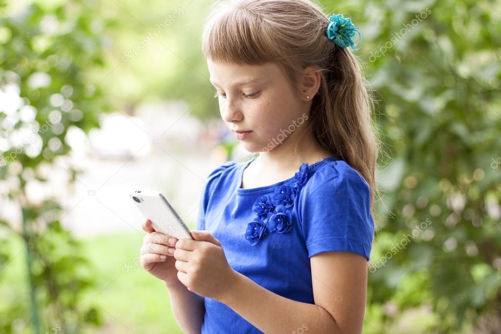 Kleine meisje zomer park praten aan de telefoon in een blauwe