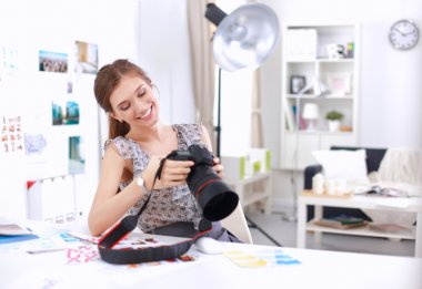 Attractive businesswoman sitting  on desk in the office with camera