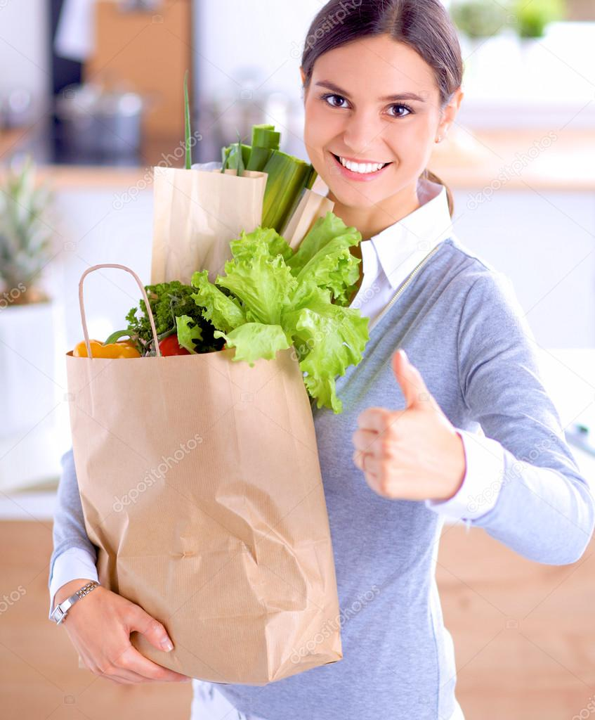 Young woman holding grocery shopping bag with vegetables .Standing in the  kitchen — Stock Photo be3c1fc3a