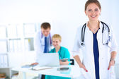 Fotografie Attractive female doctor in front of medical group
