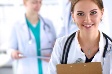 Attractive female doctor  with folder in front of medical group