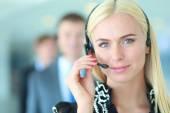 Geschäftsfrau mit Headset lächelt in die Kamera im Callcenter. Geschäftsleute mit Kopfhörern im Hintergrund