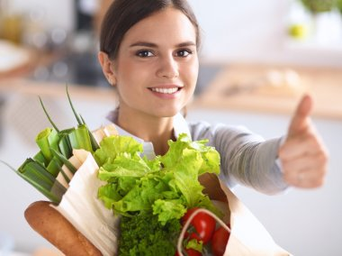 Young woman holding grocery shopping bag with vegetables and showing ok