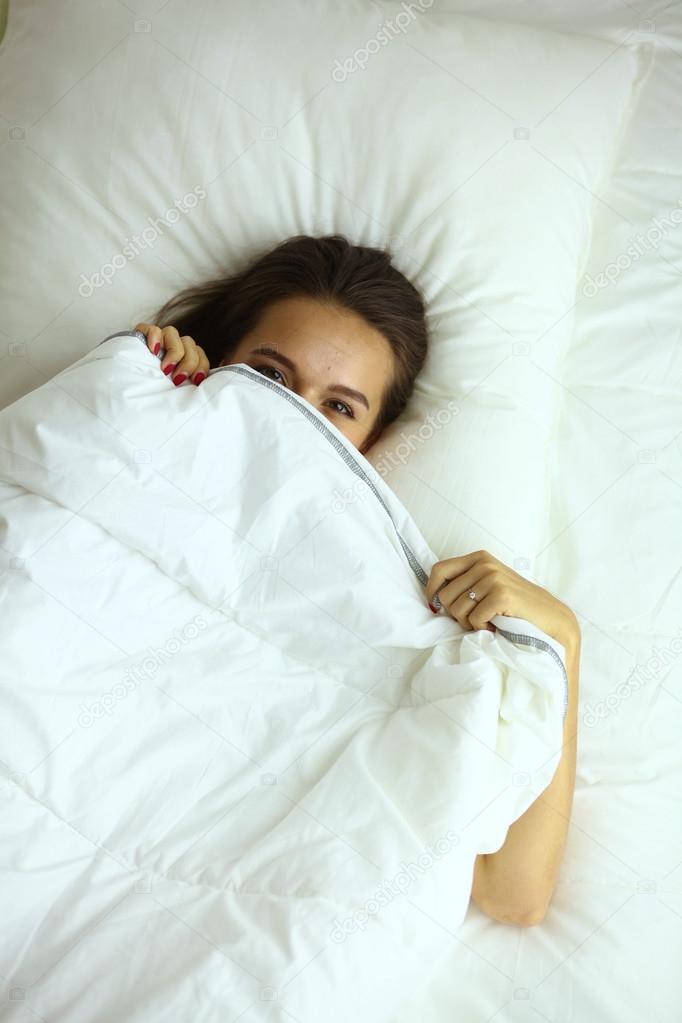Een mooie jonge vrouw onder de covers in haar slaapkamer happilly ...