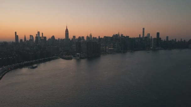 AERIAL: over East River kilátással Manhattan New York City Skyline gyönyörű Dawn Sunset Orange Light