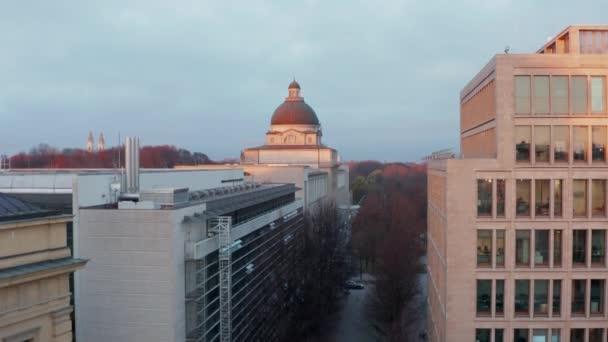 Das Gebäude der Bayerischen Staatsregierung oder Staatskanzlei in München, Deutschland im wunderschönen Sonnenuntergang mit Blick über den Englischen Garten im Winter, Luftkran ragt in die Höhe und verrät das Stadtbild