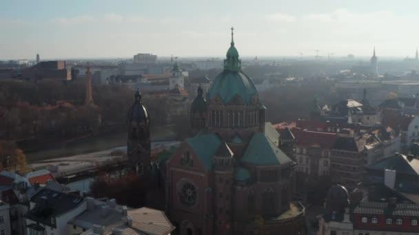 Malerischer Blick auf eine Kathedrale im Wintersonnenlicht mit begrüntem Dach und Kirchturm in München, Deutschland Nachbarschaft direkt am Fluss Isa