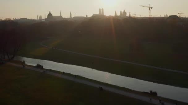 Fluss fließt durch Englischen Garten Öffentlicher Park in München mit Blick auf City Skyline im schönen Wintersonnenlicht, Antenne kippt Deutschland