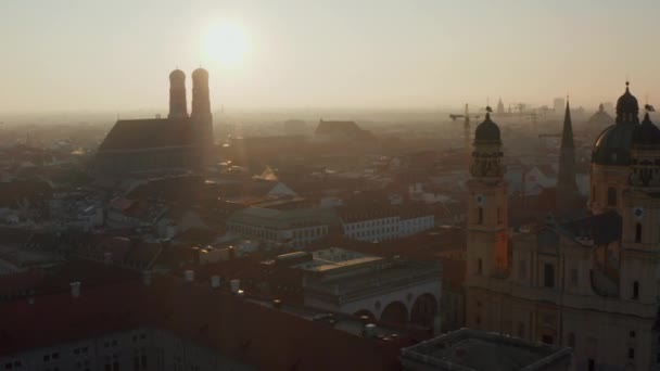 Nachmittagssonne lugt an einem Wintertag durch das Münchner Stadtbild mit der Silhouette der Frauenkirche, langsam nach vorne gekippt