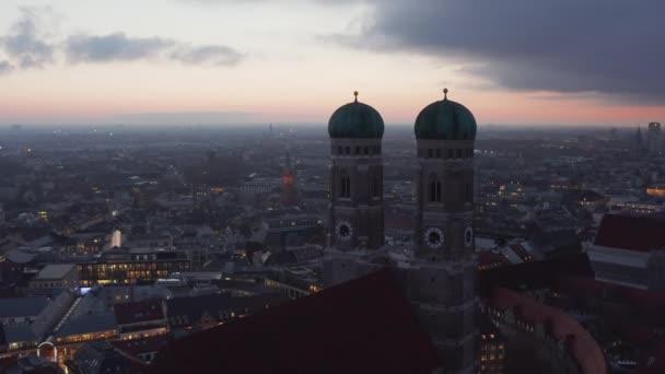 Vorbei an den beiden Türmen der Frauenkirche in München, Deutschland bei Sonnenuntergang mit Stadtbeleuchtung in der Ferne, Scenic Air Cinematic Shot