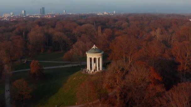 Epic Scenic Aerial Dia Circle rund um die Monopteros im Englischen Garten in München, Deutschland, umgeben von wunderschönen Orangenbäumen im öffentlichen Park mit grünem Gras, Aerial Dolly Slide rechts