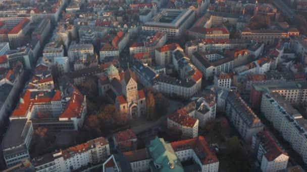 Kirchenkathedralenbau inmitten der deutschen Wohngegend in München, Bayern, Szenische Luftrutsche nach rechts über rote Dächer gekippt