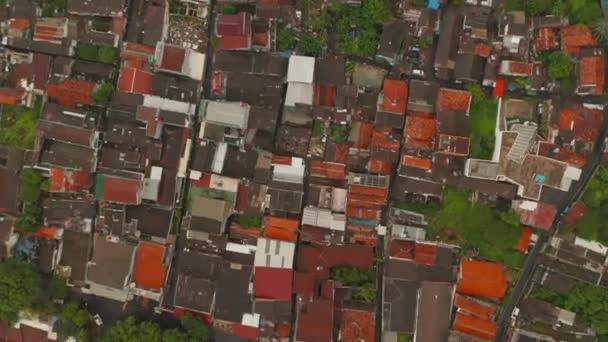 Légi forgó Birds Eye Overhead Top Down Kilátás élénk piros és narancssárga háztetők sűrű városi környéken Jakarta