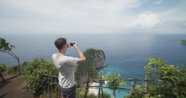 Wieder aufsteigender Blick eines männlichen Touristen, der die Halbinsel T-Rex Bay am Kelingking Strand in Bali, Indonesien, mit seinem Handy fotografiert