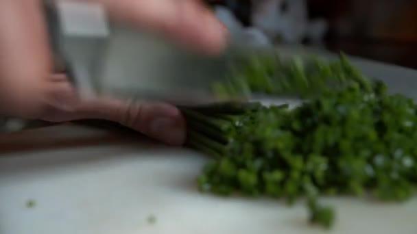 Zblízka pohled na nůž řezání více pažitka na hromadu malých zeleninových kousků. Příprava zelené zeleniny na kuchyňském stole