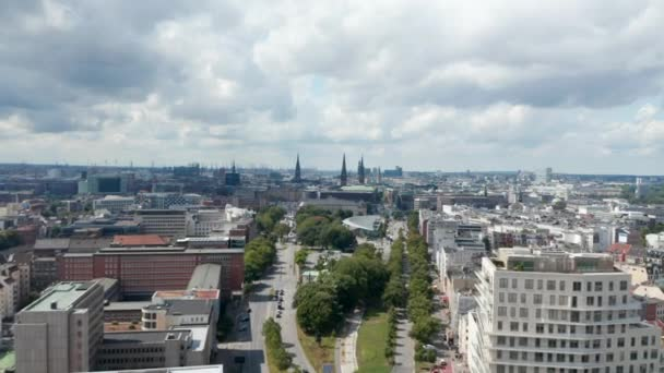 Luftaufnahme eines Stadtviertels, das in Richtung historisches Stadtzentrum mit Kirchtürmen fliegt. Hafenkräne im Hintergrund. Freie und Hansestadt Hamburg, Deutschland
