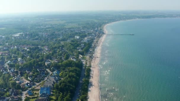 High aerial drone view of scenic summertime beach in Scharbeutz, Germany, dolly in, sunny windy day