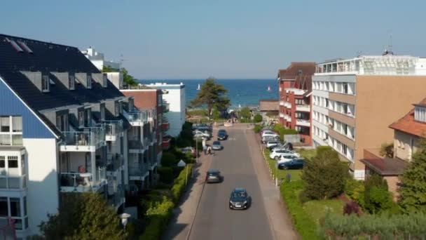 Aerial view flying between building street facing Baltic clear blue sea water in Scharbeutz, Germany, dolly in, day