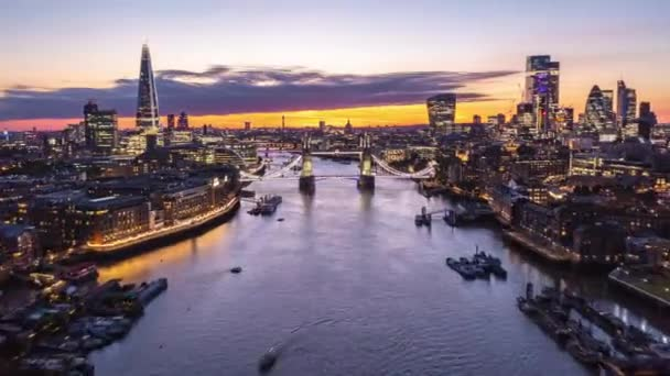 Forwards reveal of city lights of large town at dawn. Amazing hyperlapse of fly over Tower Bridge. Modern skyscrapers on both Thames river banks. London, UK