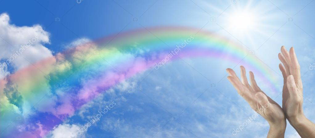 Panoramic blue sky with sunburst, rainbow and two hands reaching up