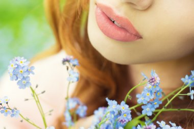 Big sexy lips girls with blue flowers in her hands