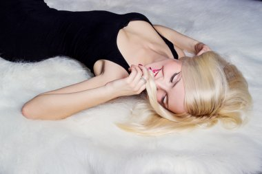 Beautiful sexy happy women blonde with a smile lying on the white carpet in a black dress