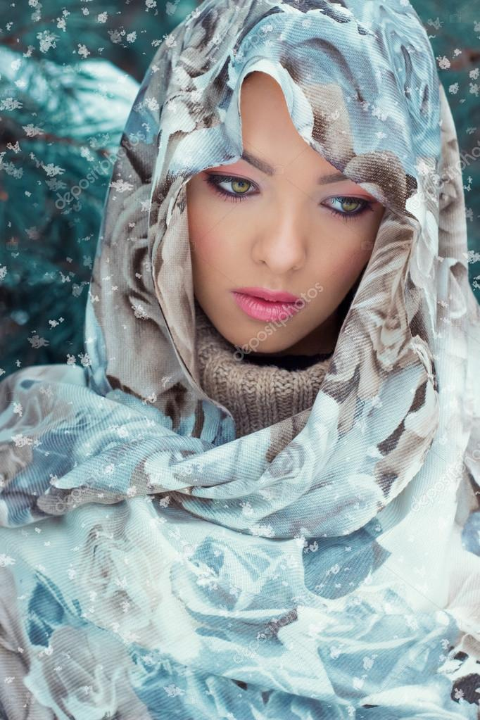 Beautiful young sexy mysterious woman with a scarf on her head standing in the forest near the oil in bright winter day