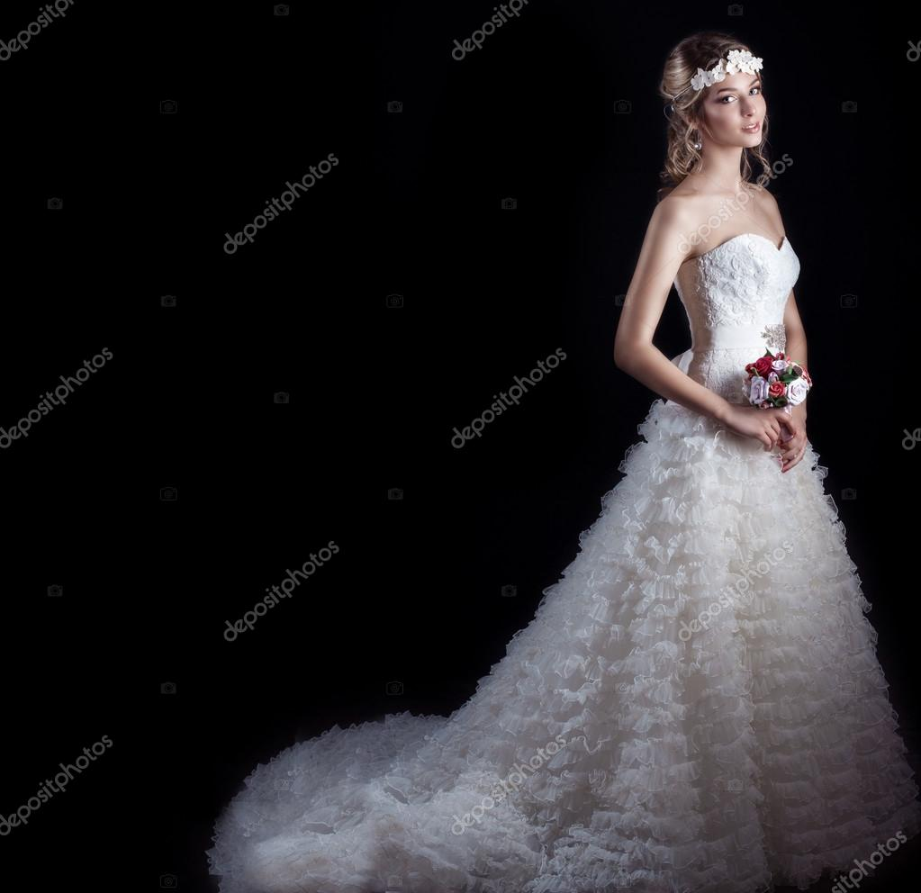 Beautiful gentle woman happy bride in a white wedding dress with a train cabin with a beautiful wedding hairstyle with white flowers in her hair and a small bouquet in her hands