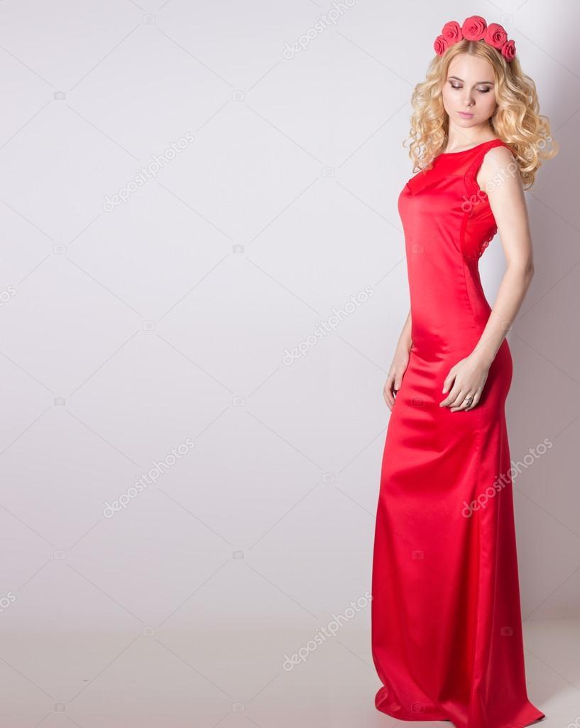 Schöne sexy blonde Mädchen in roten langen Abendkleid mit Blüten in ...