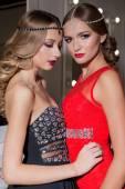 Fotografie zwei schöne sexy elegante Mädchen in einem roten und schwarzen Abendkleidern mit hellen Abend Make-up Abend Frisur und Zecken auf dem Kopf in der Studio-Umkleidekabine in einem festlichen Abend