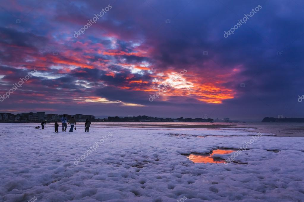 Red sky sunset over snowy Poole beach