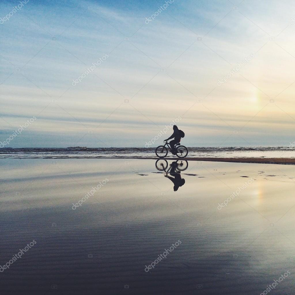 Man riding bicycle on seashore