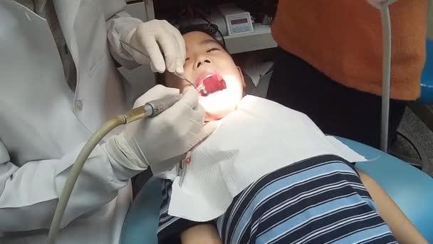 Kleiner Junge, der seinen Mund während der Untersuchung der Mundhöhle weit öffnete