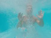 Mladý muž topící se pod vodou v moři nebo oceánu, modrá voda s bublinami