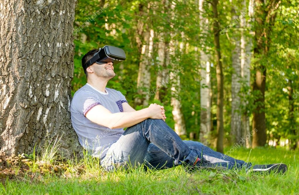 Man wearing virtual reality headset in park