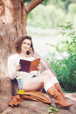 Portrait of beautiful white Caucasian girl woman with long dark red brown hair, in shorts and sweater, sitting in summer park forest outside reading book dreaming, looking up, toned with Instagram filters