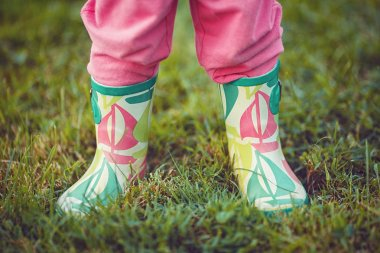 Closeup view of child legs in rain boots