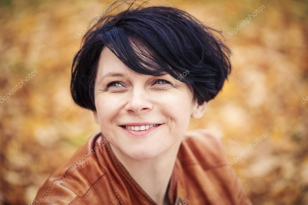 brunette middle aged woman outside in autumn park