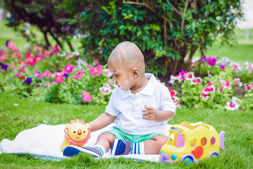 Portrait of cute adorable little indian South Asian infant boy in white  shirt sitting on ground with toys in park green grass blanket outside on  bright ... baed43be022ae