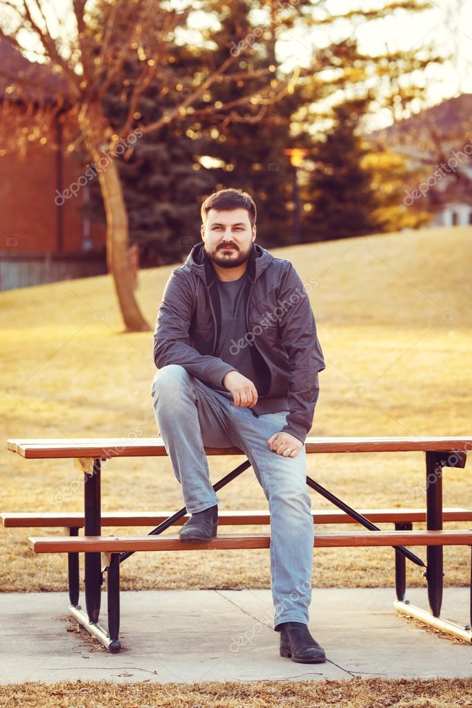 Young bearded man sitting on bench